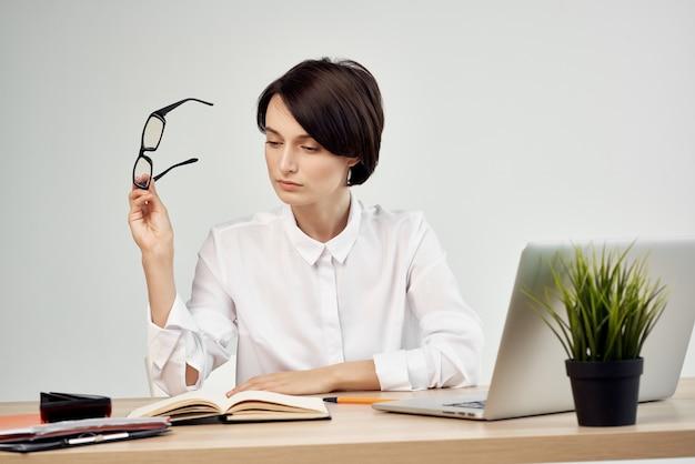 Mulher de negócios de óculos na frente da mesa do laptop