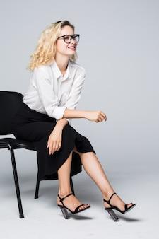 Mulher de negócios de óculos sentada em uma cadeira isolada na parede branca