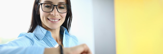 Mulher de negócios de óculos sorri e olha para o relógio