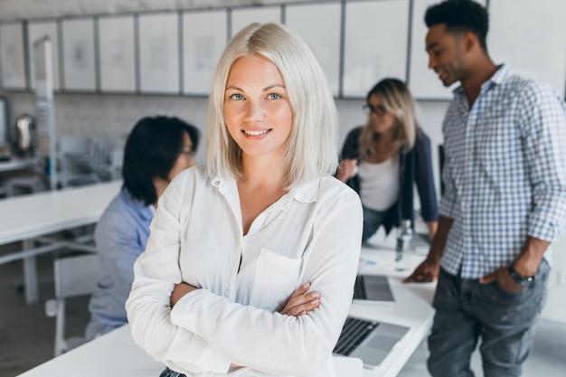 Mulher de negócios de olhos azuis em uma blusa branca em pose confiante com seus colegas de trabalho internacionais. retrato interno de funcionários asiáticos e africanos com uma senhora loira.