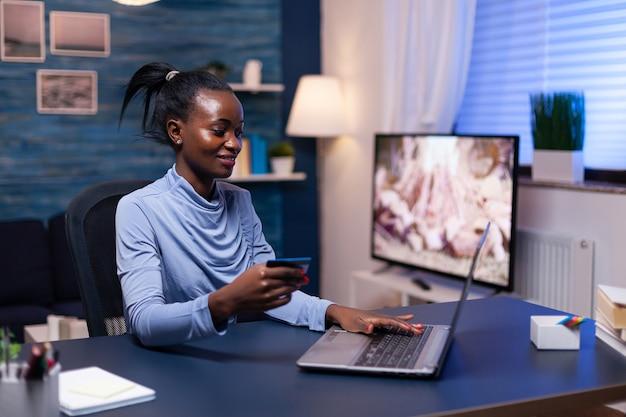 Mulher de negócios de pele escura, segurando o cartão de crédito, fazendo compras financeiras para empresas a partir do escritório em casa. funcionário que faz a transação do paymant em casa no notebook digital.