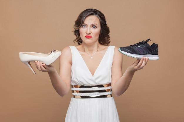 Mulher de negócios de pensamento duvidoso, de vestido branco em pé, segurando elegantes sapatos de salto alto e tênis confortáveis e não sabe qual escolher. foto de estúdio, interna, isolada em fundo marrom claro