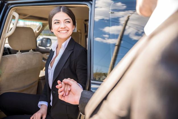 Mulher de negócios de sorriso bonita nova no terno que sai.