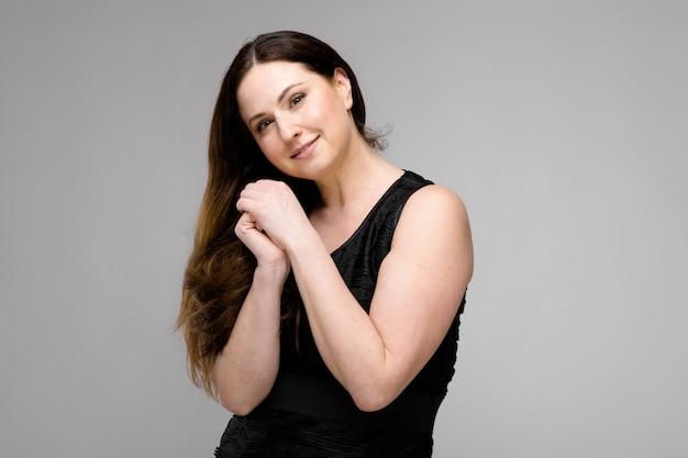 Mulher de negócios de sorriso caucasiano moreno positiva nova atrativa bonita no vestido preto isolado na cinza