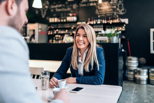 Mulher de negócios de sorriso que come uma xícara de café com um colega.