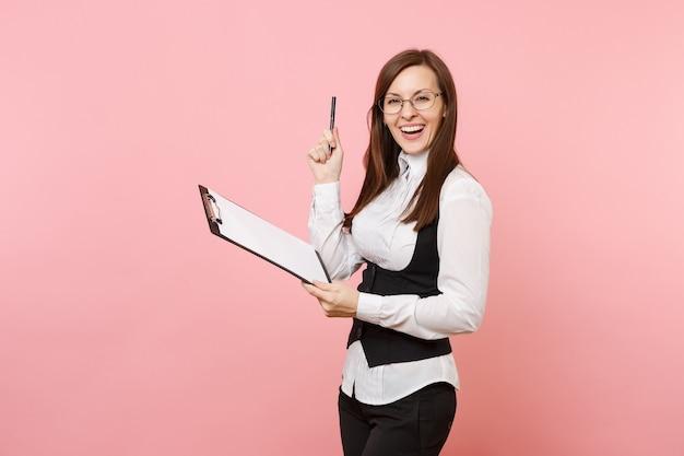 Mulher de negócios de sucesso alegre jovem em copos segurando o tablet da área de transferência com documentos de papel e caneta isolado no fundo rosa. senhora chefe. riqueza de carreira de realização. copie o espaço para anúncio.