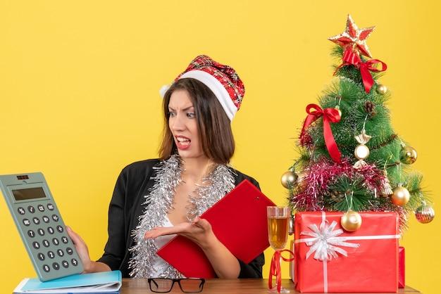 Mulher de negócios de terno com chapéu de papai noel e decorações de ano novo, apontando calculadora e sentada em uma mesa com uma árvore de natal nela no escritório