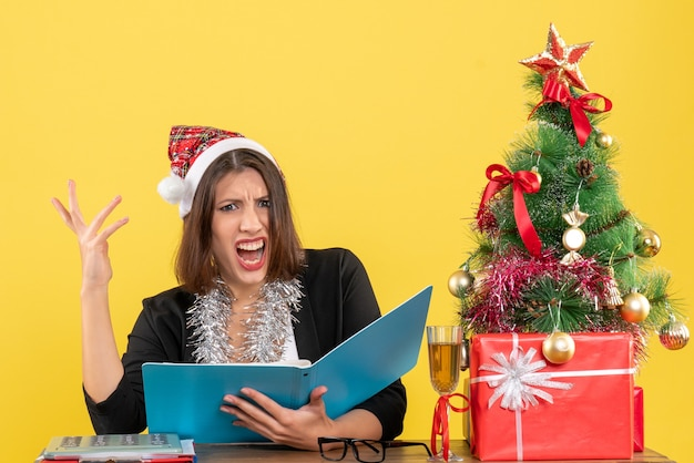 Mulher de negócios de terno com chapéu de papai noel e decorações de ano novo focada no documento e se sentindo confusa e sentada em uma mesa com uma árvore de natal no escritório