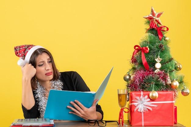 Mulher de negócios de terno com chapéu de papai noel e decorações de ano novo focada no documento e sentada em uma mesa com uma árvore de natal no escritório