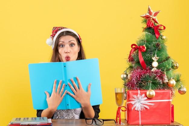 Mulher de negócios de terno com chapéu de papai noel e decorações de ano novo focada no documento em pensamentos profundos e sentada em uma mesa com uma árvore de natal no escritório