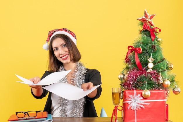 Mulher de negócios de terno com chapéu de papai noel e decorações de ano novo, mostrando documentos e sentada em uma mesa com uma árvore de natal no escritório