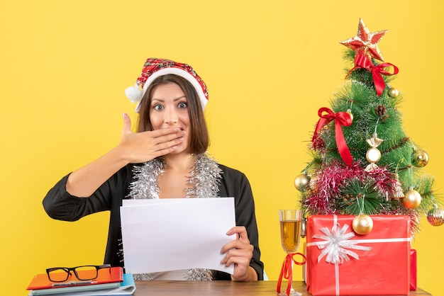 Mulher de negócios de terno com chapéu de papai noel e decorações de ano novo olhando para algo surpreendente e sentada em uma mesa com uma árvore de natal no escritório