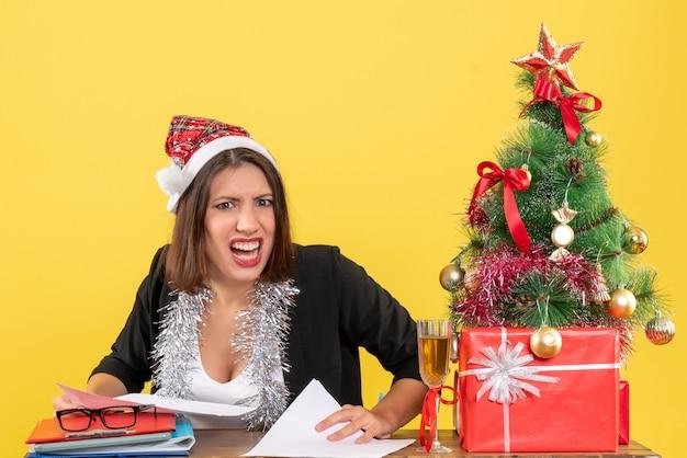 Mulher de negócios de terno com chapéu de papai noel e decorações de ano novo, sentindo raiva e sentada em uma mesa com uma árvore de natal no escritório