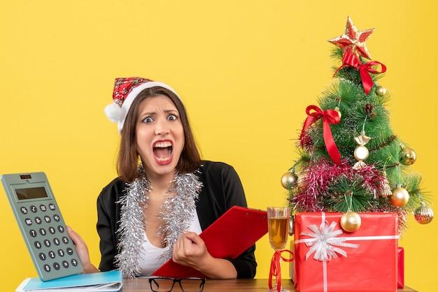 Mulher de negócios de terno com chapéu de papai noel e decorações de ano novo, sentindo-se confusa enquanto verificava a contabilidade e se sentava em uma mesa com uma árvore de natal no escritório