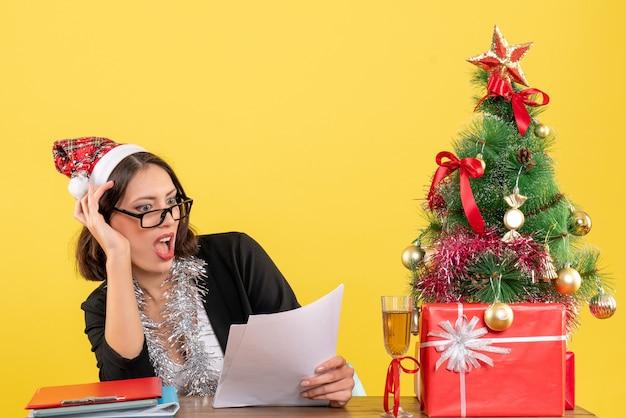 Mulher de negócios de terno com chapéu de papai noel e decorações de ano novo, sentindo-se emocionada e sentada em uma mesa com uma árvore de natal no escritório