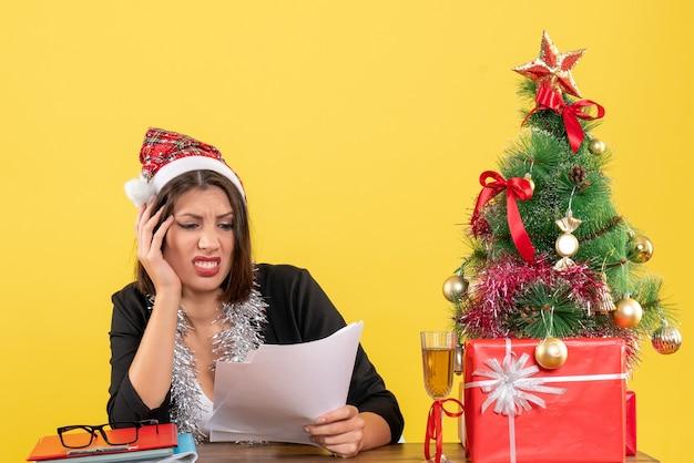 Mulher de negócios de terno com chapéu de papai noel e decorações de ano novo, sentindo-se exausta e sentada em uma mesa com uma árvore de natal no escritório