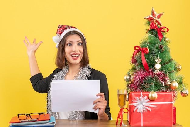 Mulher de negócios de terno com chapéu de papai noel e decorações de ano novo trabalhando sozinha, apontando para trás segurando documentos e sentada em uma mesa com uma árvore de natal no escritório