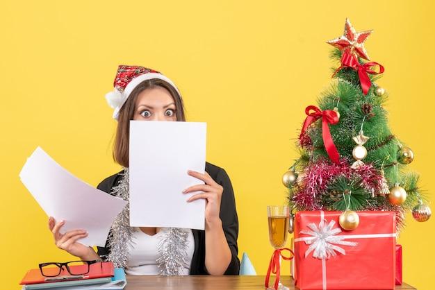 Mulher de negócios de terno com chapéu de papai noel e decorações de ano novo verificando documentos de forma surpreendente e sentada em uma mesa com uma árvore de natal no escritório