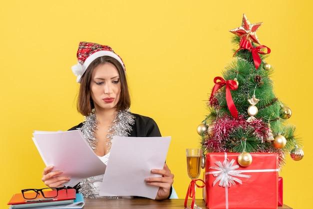 Mulher de negócios de terno com chapéu de papai noel e decorações de ano novo, verificando documentos e sentada em uma mesa com uma árvore de natal no escritório