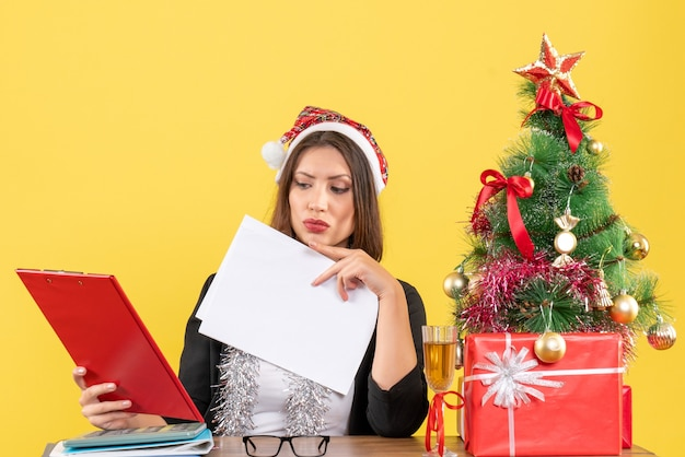 Mulher de negócios de terno com chapéu de papai noel e decorações de ano novo, verificando o documento e sentada à mesa com uma árvore de natal no escritório