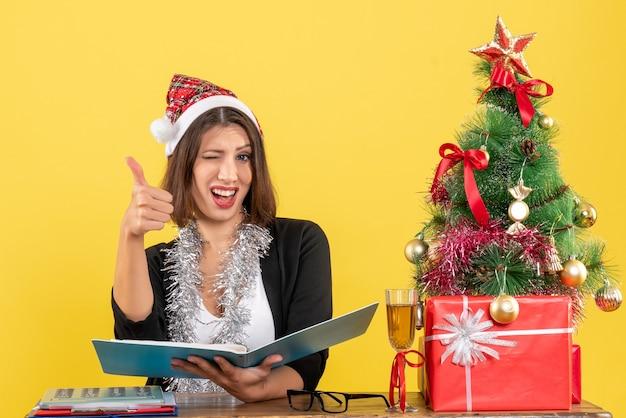 Mulher de negócios de terno com chapéu de papai noel e decorações de ano novo, verificando o documento, fazendo um gesto de ok e sentada em uma mesa com uma árvore de natal no escritório