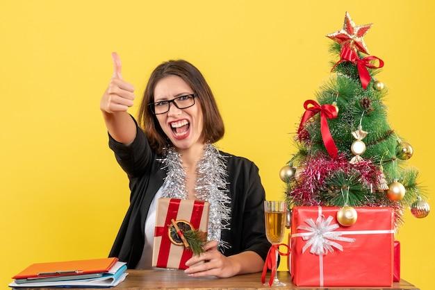 Mulher de negócios de terno com óculos segurando seu presente, fazendo um gesto de ok e sentada em uma mesa com uma árvore de natal no escritório