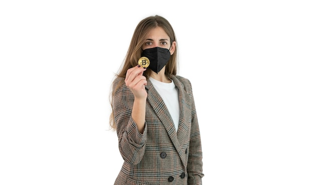 Mulher de negócios de terno e máscara segurando um bitcoin com a mão isolada