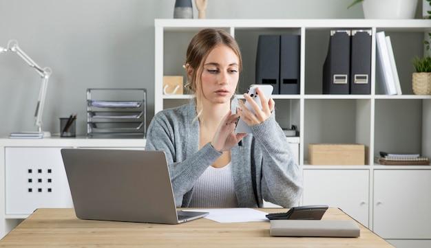 Mulher de negócios de tiro médio segurando o telefone