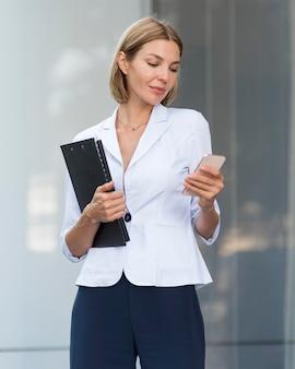 Mulher de negócios de tiro médio verificando o telefone