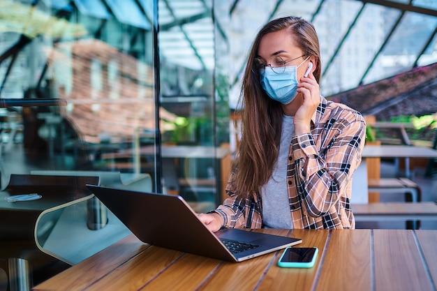 Mulher de negócios de trabalho casual na máscara facial, fones de ouvido sem fio brancos e óculos trabalha remotamente no computador no café. distância social e proteção da saúde em locais públicos