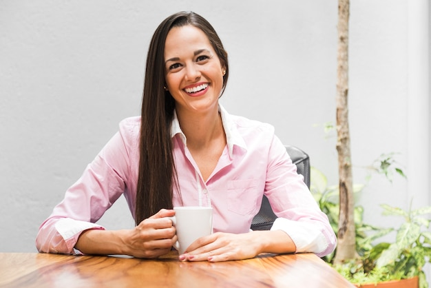 Mulher de negócios de vista frontal com uma xícara de café
