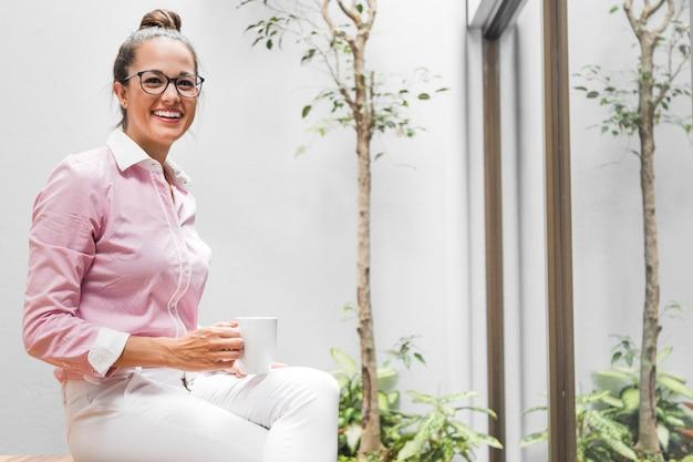 Mulher de negócios de vista frontal sentado em um banquinho