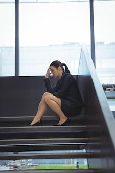 Mulher de negócios deprimida com a mão na cabeça sentada na escada