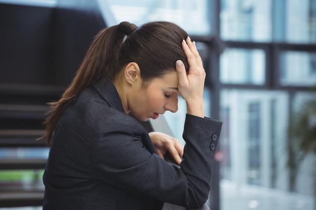 Mulher de negócios deprimida com a mão na cabeça
