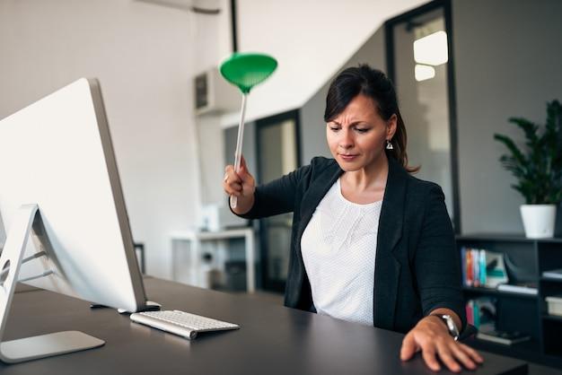 Mulher de negócios determinada com um mata-moscas.