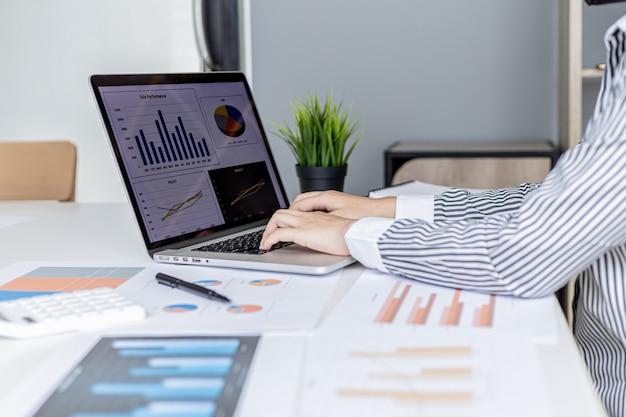 Mulher de negócios digitando em um teclado de laptop, ela está preparando um resumo financeiro para levar para uma reunião com parceiros de negócios. conceito de gestão financeira da empresa. verificando informações financeiras.