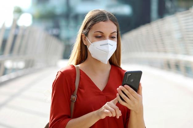 Mulher de negócios digitando em um telefone inteligente em uma cidade moderna usando máscara facial