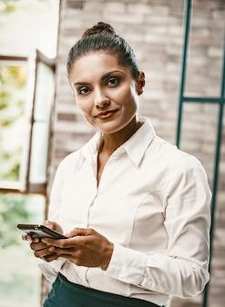 Mulher de negócios, digitando mensagens de texto no telefone inteligente