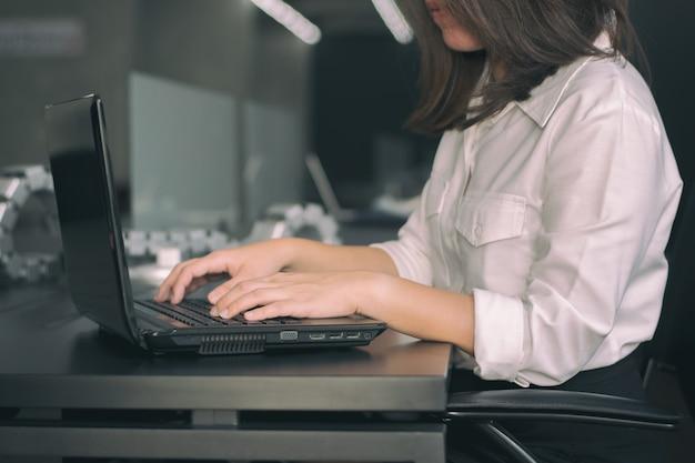 Mulher de negócios, digitando no teclado do laptop