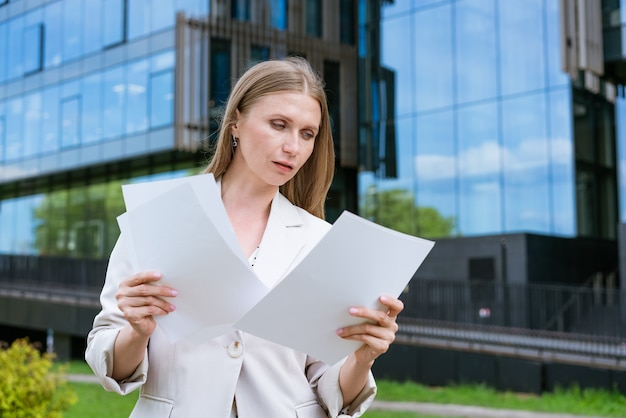 Mulher de negócios, diretora executiva de sucesso lê documentos em papel com uma jaqueta leve de pé sobre o ...