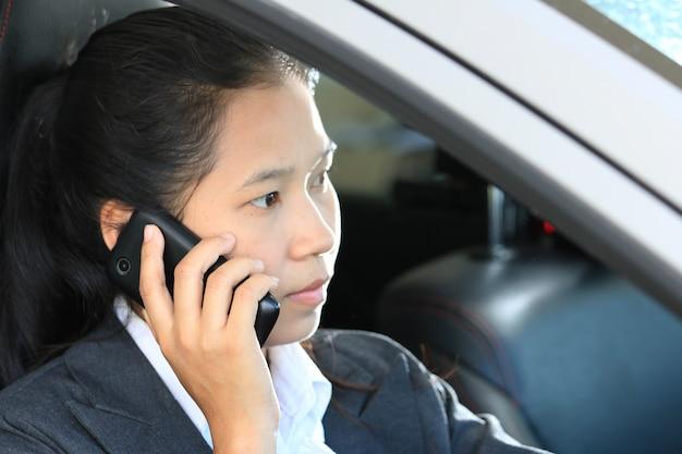 Mulher de negócios, dirigindo o carro e falando de um telefone