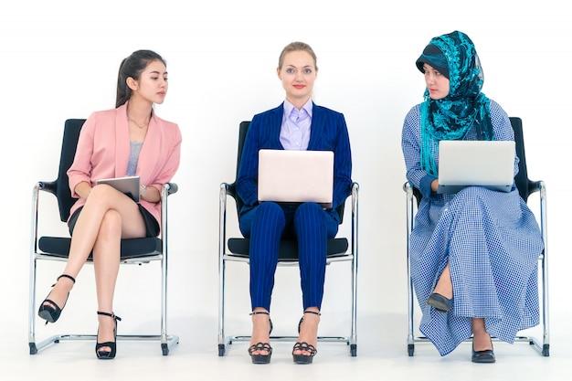 Mulher de negócios diversos é a inveja de uma mulher caucasiana em reunião