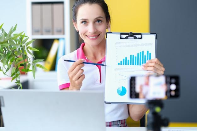 Mulher de negócios do blogger mostra indicadores financeiros na câmera no relatório de negócios de análise de gráficos
