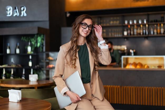 Mulher de negócios dona de restaurante com laptop nas mãos vestida elegante macacão em pé no restaurante com balcão de bar branco óculos feminino pessoa de negócios interna