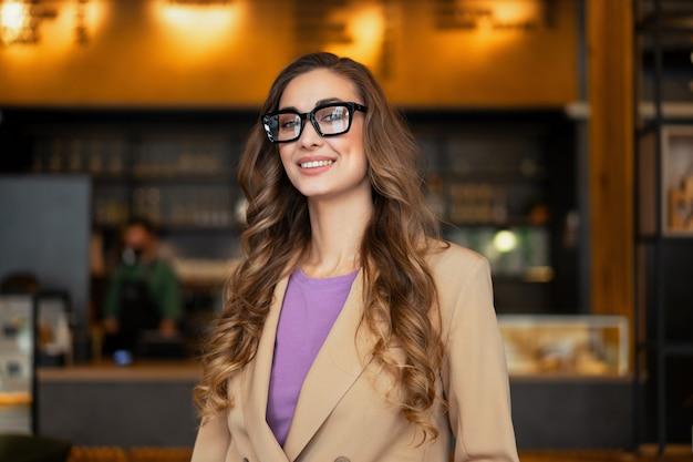 Mulher de negócios dona de restaurante com macacão elegante em pé no restaurante com superfície de balcão de bar caucasiano feminino óculos pessoa de negócios interna