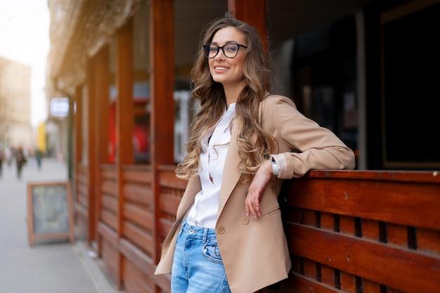 Mulher de negócios dona de restaurante com macacão elegante em pé perto de um restaurante ao ar livre caucasiana mulher óculos pessoa de negócios
