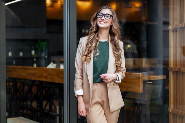 Mulher de negócios dona de restaurante com macacão elegante em pé perto de um restaurante grande janela ao ar livre caucasiana óculos femininos pessoa de negócios