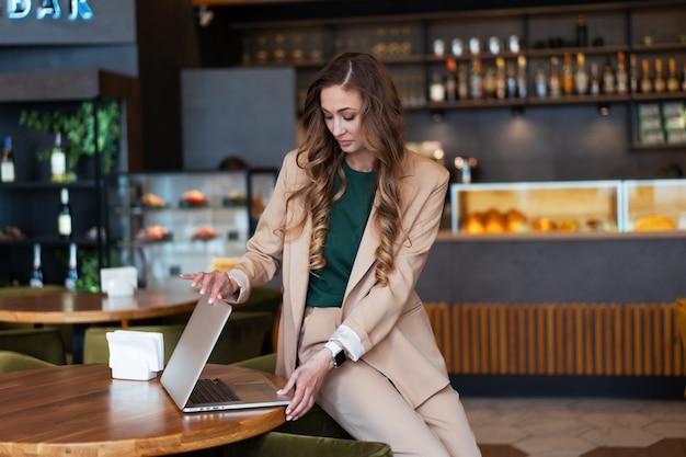 Mulher de negócios dona de restaurante usa laptop nas mãos vestida elegante macacão sentado na mesa no restaurante com fundo de balcão de bar branca pessoa de negócios interna
