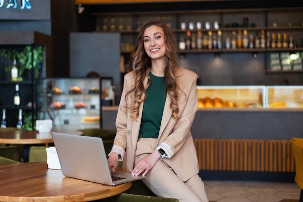 Mulher de negócios dona de restaurante usa laptop nas mãos vestida elegante macacão sentado na mesa no restaurante com superfície do balcão de bar caucasiano feminino pessoa de negócios interna