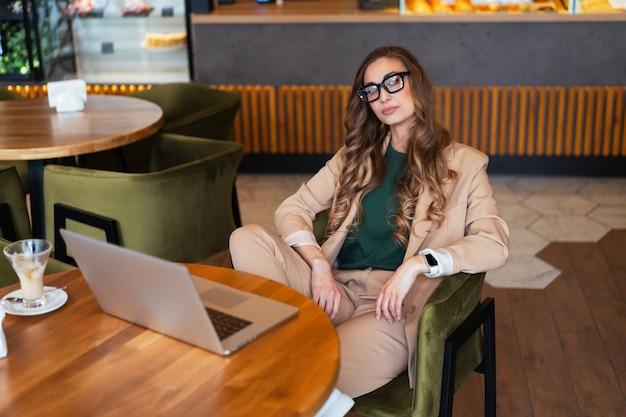 Mulher de negócios dona de restaurante usa laptop vestido elegante macacão sentado na mesa no restaurante com balcão de bar caucasiana feminina pessoa de negócios interna
